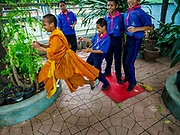 20 SEPTEMBER 2017 - BANGKOK, THAILAND: A Buddhist novice at recess with his classmates at Wat  Ratchruek School along Khlong Bangkok Yai in the Thonburi section of Bangkok. Most Thai males join the Sangha (Buddhist clergy) at least once in their lives, sometimes for only a few weeks.      PHOTO BY JACK KURTZ