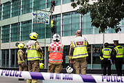 London Fire Brigade firefighters observe two climate activists from HS2 Rebellion who scaled the Marsh insurers building in the City of London in protest against the HS2 high-speed rail project on 2nd September 2021 in London, United Kingdom. Marsh JLT Specialty are the main insurers for HS2.