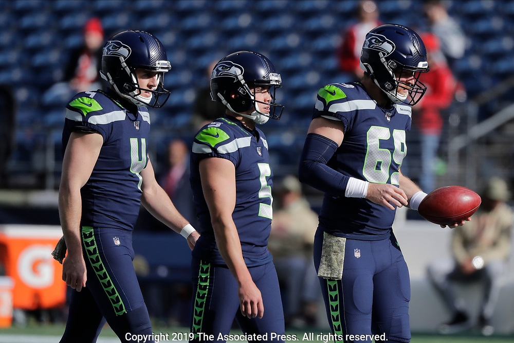Seattle Seahawks long snapper Tyler Ott, right, walks with punter Michael Dickson, left, and kicker Jason Myers, center, during warmups before an NFL football game against the Tampa Bay Buccaneers, Sunday, Nov. 3, 2019, in Seattle. (AP Photo/John Froschauer)