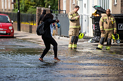© Licensed to London News Pictures. 24/06/2021. London, UK. A member of the public takes off her shoes to wade through water in St John's Wood, North London, where a burst pipe has has cause flooding across a number of streets in the area. Photo credit: Ben Cawthra/LNP