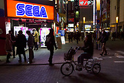 A young woman rides a tricycle past the Sega store in Akihabara, Tokyo, Japan. Friday January 26th 2018