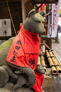A statue of Inari Kitsune or fox goddess, wearing a red bib believed to expel demons at the Toyokawa Inari Betsuin temple in Asakusa, Tokyo, Japan. The Buddhist temple is part of the Soto Zen sect and enshrines the deity Toyokawa Dakinishinten but also known for the thousands of fox statues.