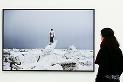 "© Licensed to London News Pictures. 14/03/2019. London, UK. A woman views a photograph of Murmansk, Kola Peninsula, Russia September 2018.<br /> Carmignac Photojournalism award - ""Arctic - New Frontier"" exhibition by Yuri Kozyrev and Nadir Vab Lohuizen on show at Saatchi Gallery. Yuri Kozyrev and Kadir van Lohuizen (NOOR) were awarded the 9th edition of the Carmignac Photojournalism Award dedicated to the Arctic. The endowment allowed them to carry out their pioneer double polar expedition 'Arctic: New Frontier'. <br /> The exhibition runs from 15 March, it will run until 5 May 2019 at Saatchi Gallery. Photo credit: Dinendra Haria/LNP"