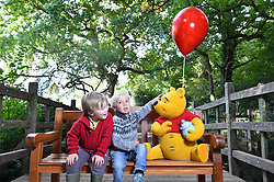 EDITORIAL USE ONLY<br /> Three year old Ed Clayton (left) and Jacob O'Dell, four, sit on a bench, known as a 'Thotful Spot', that talks to you when you sit on it, at '100 Acre Woods' in Ashdown Forest, to celebrate the 90th anniversary of the publication of AA Milne's first collection of stories about Winnie-the-Pooh this Friday.