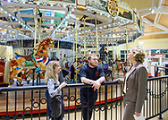 "Garden City, New York, USA. March 9, 2019.  L-R, Carousel operators BETH ORBERG and her son ANDREW OBERGH and Nassau County Executive LAURA CURRAN talk at railing around Nunley's Carousel, during Unveiling Ceremony of mural of a Nunley's Carousel horse. The Obergh family runs the carousel, and raised $85,000 for ""Pennies for Ponies"" campaign to help restore the horses. Event was held at historic Nunley's Carousel in its Pavilion on Museum Row on Long Island."