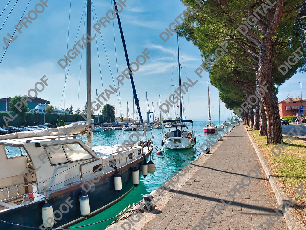 Sailboats anchored along the lungolago Giuseppe Garibaldi in the village of Peschiera del Garda on Lake Garda, Italy on a sunny summer afternoon