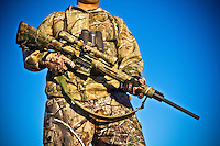 DETAILS OF A HUNTER WITH A REMINGTON R-15 RIFLE REALTREE AP CAMO