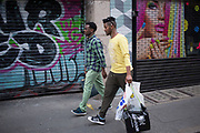 Street scene along Berwick Street with passers by interacting with graffiti and the colourful closed shutters of local shops in Soho, London, England, United Kingdom. (photo by Mike Kemp/In Pictures via Getty Images)