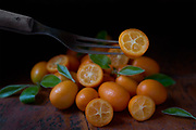 Kumquats by Rodney Bedsole, a food photographer based in Nashville. Food image of sliced kumquats with leaves on a wood surface.
