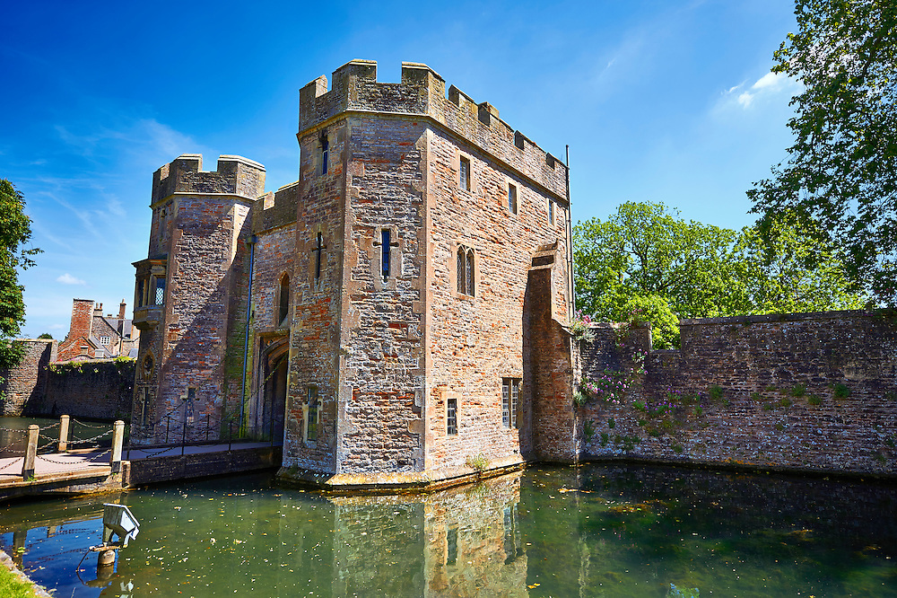 """Gate House and moat of the Bishops Palace of the the medieval Wells Cathedral built in the Early English Gothic style in 1175, Wells Somerset, England . Its Gothic architecture is mostly in Early English style of the late 12th – early 13th centuries. Building began about 1175 at the east end with the choir. Historian John Harvey sees it as Europe's first truly Gothic structure. Its Early English front with 300 sculpted figures, is seen as a """"supreme triumph of the combined plastic arts in England"""".<br /> <br /> Visit our MEDIEVAL PHOTO COLLECTIONS for more   photos  to download or buy as prints https://funkystock.photoshelter.com/gallery-collection/Medieval-Middle-Ages-Historic-Places-Arcaeological-Sites-Pictures-Images-of/C0000B5ZA54_WD0s"""