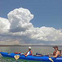 Yellowstone National Park. Kayakers on Yellowstone Lake, under summer thunderstorm cloud, Wyoming