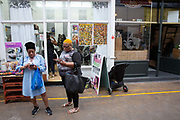 Two women outside a hairdressers using their mobile phones at Brixton Village on the 23rd May 2019 in London in the United Kingdom.
