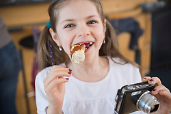Portrait of girl with camera and eating pretzel, smiling