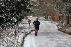 © Licensed to London News Pictures. 08/02/2021. Surrey, UK. A member of the public runs through snow covered woods and roads on Box Hill in Surrey this morning as Storm Darcy hits the South East with more snow and freezing temperatures today. The Met Office have issue numerous weather warnings for heavy snow and ice with disruption to travel, power cuts and possible stranded vehicles as the bad weather continues.  Photo credit: Alex Lentati/LNP