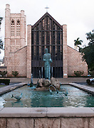 A statue sits in front of a church in downtown Honolulu.
