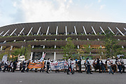Police escort people taking part in a demonstration against the delayed 2020 Tokyo Olympics Games in Gaiemmae, Tokyo, Japan. Sunday May 9th 2021. About 100 people took part in a demo outside the Japanese Olympic Committee museum and marched around the new Olympic Stadium to protest holding the event while the  the COVID-19 pandemic is still seriously affecting Japan.