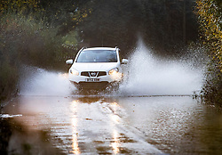 © Licensed to London News Pictures. 14/11/2019. Charlwood, UK.  Cars drive through flooding on a road near Charlwood in West Sussex. Environment Agency flood warning alerts are in place for homes near Ifield Brook and the River Mole nearby. Photo credit: Peter Macdiarmid/LNP