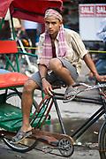 A young rickshaw wallah rests on Chadni Chowk, Old Delhi, India