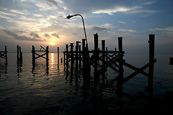 29 August 2006. New Orleans, Louisiana. Lakeview. Lake Pontchartrain. The ruins of a fishing pier reflect in the still waters that just 12 months ago devastated the area as they filled back into the city, rupturing the nearby 17th street canal. The connection New Orleans and south Louisiana has with the water is inextricable. The two are forever linked together and until the Army Corps of Engineers is able to build sufficient flood protection, and the greater world is able to control global warming and rising seas, the city and the region will continue to be at increased risk for even greater devastation in the years ahead.<br /> Photo Credit©; Charlie Varley/varleypix.com