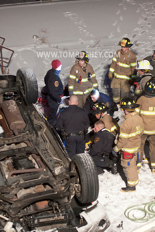 Middlletown, New York - Middletown firefighters and police work at the scene of a motor vehicle accident on Dec. 31, 2013. A vehicle went through a fence and landed upside down in a play area at the former Memorial School. A snow squall had left the roads very slippery. The driver was trapped inside the vehicle.