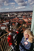 Tourists look at the view from the top of Steeple of vor Freslers Kirke. Copenhagen, Denmark.