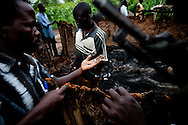 A group of Arrow boys inspect Tereza Polino's burnt home outside of Tambura after the LRA attacked.