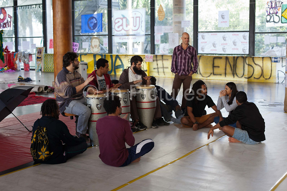 Drum circle in the main space. The Ministry of Culture in Rio de Janeiro has been occupied since 15th May 2016. Originally as a protest in response to the interim President Michel Temer cutting the Ministry, even though it has been re-instated, the occupation continues. Dozens of protesters are resident here, living in tents shelters inside the building. The space has been host to a multitude of self organised cultural events, from music to discussions to yoga, and even some University lecturers holding their classes here, it is a hotbed of activity.