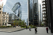 Angled view of the cityscape and skyline reflections looking towards 1 St Mary Axe aka the Gherkin as skateboarders interact in the quiet urban landscape on 26th May 2021 in London, United Kingdom. As the coronavirus lockdown continues its process of easing restrictions, the City remains far quieter than usual, which asks the question if normal numbers of people and city workers will ever return to the Square Mile.
