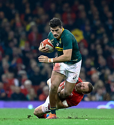 Damian de Allende of South Africa is tackled by Hadleigh Parkes of Wales<br /> <br /> Photographer Simon King/Replay Images<br /> <br /> Under Armour Series - Wales v South Africa - Saturday 24th November 2018 - Principality Stadium - Cardiff<br /> <br /> World Copyright © Replay Images . All rights reserved. info@replayimages.co.uk - http://replayimages.co.uk