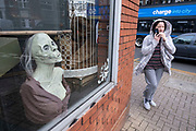 Gruesome horror mannaquin in the window as a woman passes by a second hand shop selling all manner of curiosities in Kings Heath on 23rd November 2020 in Birmingham, United Kingdom.
