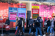 Scene of shoppers doing some last minute Christmas shopping, forming a queue outside Debenhams which is closing down along Oxford Street as the Prime Minister announces a new tighter fourth tier of local coronavirus restrictions for London and the South East, and that the planned Christmas relaxation of the rules was to be scrapped on 19th December 2020 in London, United Kingdom. These shoppers, mostly wearing face masks were unaware, as were shop owners that the new rules were about to be announced, and this would mean that all non-essential shops will have to close from midnight.