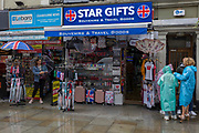 As a woman shelters under her umbrella, a tourist family put on plastic rain macs in front of a souvenir shop selling travel gifts in Central London, on 15th June 2019, in London, England.