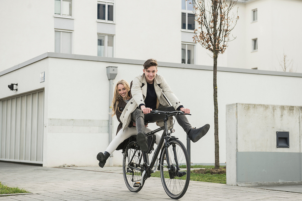 Young couple riding a cycle on street, Munich, Bavaria, Germany