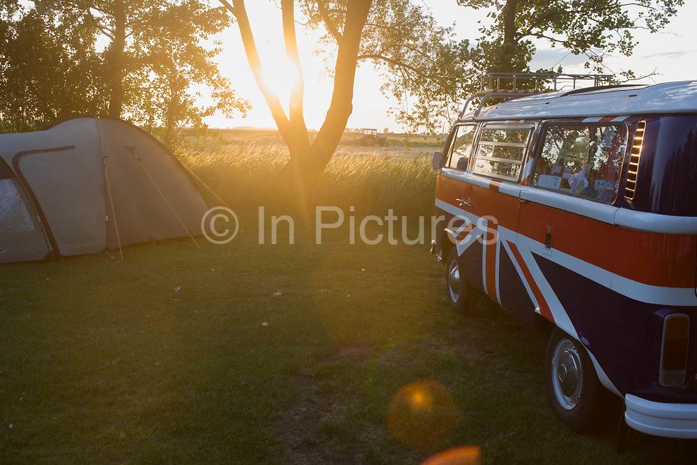 A VW camper van adorned with British union jack colours is parked on a campsite at Reedham on the Norfolk Broads. With late sun filling this field, setting to the east through a native tree, we see a tent belonging to a camper at the site in East Anglia. Painted in the colours British flag, a theme of patriotic feeling by people summing up a great, traditional British summer and their love of the countryside. The Volkswagen Type 2, known officially, depending on body type as the Transporter, Kombi and Microbus, and informally as the Bus (US) or Camper (UK), is a panel van introduced in 1950 by German automaker Volkswagen as its second car model – following and initially deriving from Volkswagen's first model, the Type 1 (Beetle), it was given the factory designation Type 2.