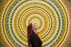 """Licensed to London News Pictures. 19/09/2019. LONDON, UK.  A staff member poses next to """"Cardinal"""" 2019, by Damien Hirst.  Preview of a new exhibition by Damien Hirst at White Cube's Mason's Yard gallery in Mayfair.  It is the artists first major solo exhibition in seven years and features large-scale concentric butterfly paintings from his new """"Mandalas"""" series.  22 large scale works are on display 20 September to 2 November 2019..  Photo credit: Stephen Chung/LNP"""