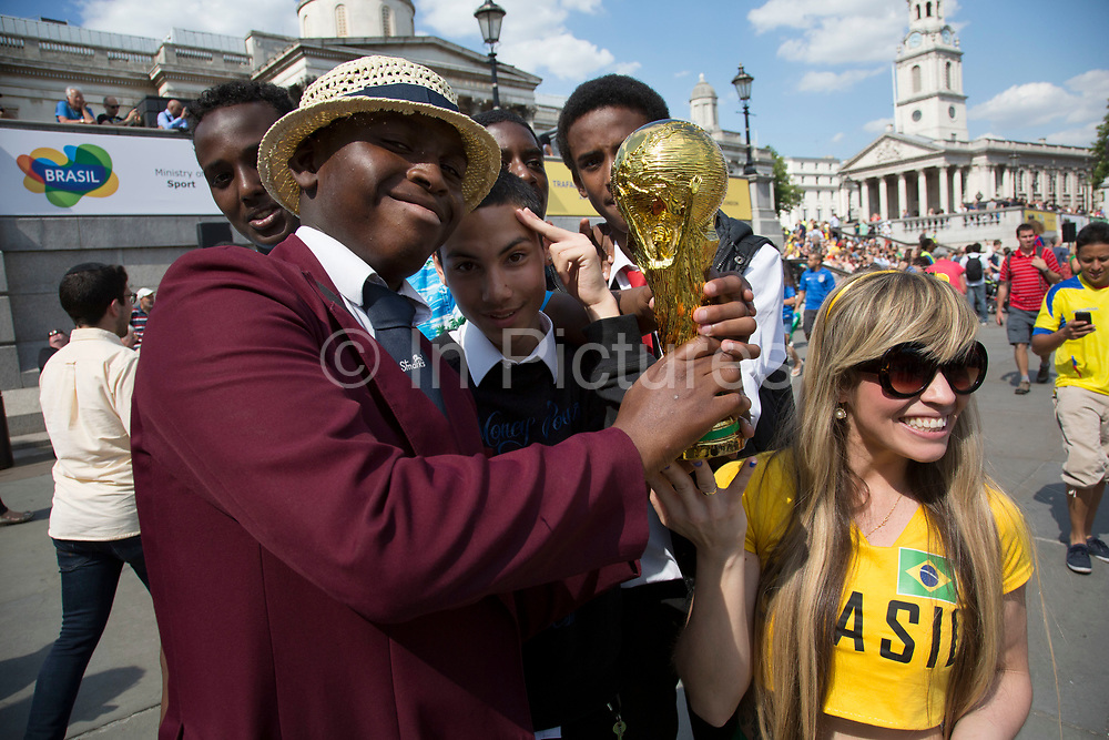 London, UK. Thursday 12th June 2014. Friends pose with a World Cup trophy. Brazilians gather for the Brazil Day celebrations in Trafalgar Sq. A gathering to celebrate the beginning of the Brazil 2014 FIFA World Cup. Revellers sing and dance and play football games and all in the yellow green and blue of the Brazilian flag.