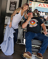Justine Ferrell from Shed Barber Shop in Austin, TX finishes up a goatee trim for Steve Costa of Westport, MA at Flo's Chop Shop in the Progressive Insurance booth on Lakeside Avenue.  Costa, a 37 year visitor to Bike Week, went for the full treatment of boot shine, shave and trim.  (Karen Bobotas/for the Laconia Daily Sun)