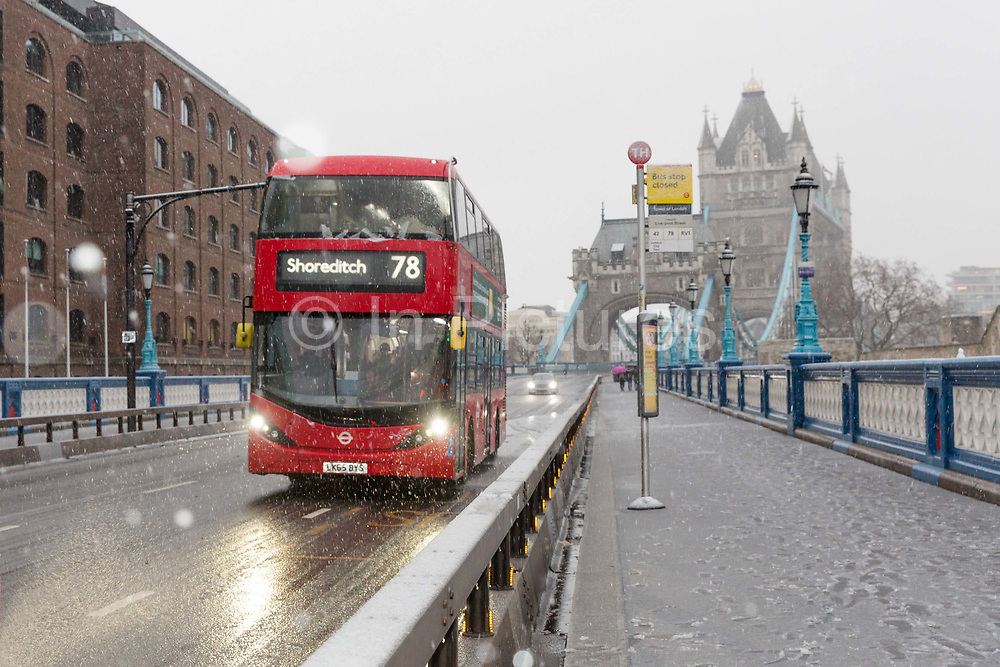 A number 78 double decker bus, destination Shoreditch, travels across Tower Bridge during a heavy snow shower on December 10th, 2017. Much of the UK has been hit by heavy snow and The Met Office have issued a yellow weather warning for snow and ice across most of the United Kingdom.