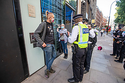 © Licensed to London News Pictures. 10/09/2020. London, UK. Burning Pink protestors glue themselves to a window at the Dept of Health. A large police presence outside the Department of Health in Victoria Street in Westminster after protestors calling themselves Burning Pink a campaigning group splatters pink paint at the entrance of the Government offices and then glues themselves to one of the front window panes this morning. Photo credit: Alex Lentati/LNP
