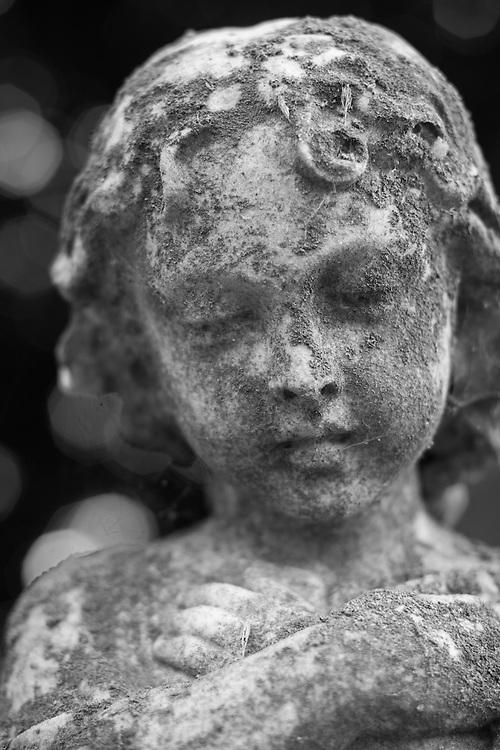 Lichen covered cemetery statue in black and white.