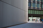 More London Place a central walkway. More London is a new development area where over the last few years of construction has resulted in a new office and business space of modern architecture. The buildings, close to each other, provide labyrinthine walkways for the workers who contain them. There are open communal areas for people to sit, and green areas likewise.