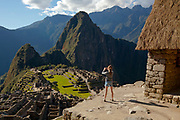 Young girl photographing the Citadel at Machu Picchu which was an Inca city in the Andes mountains