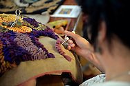 Old Bethpage, New York, USA. September 28, 2014. LORETTA SCENA, of Deer Park, is a member of LIGRA, Long Island Guild of Rugcrafting Artists, is creating a hand hooked wool pillow in the Exhibition Hall, at the 172nd Long Island Fair, a six-day fall county fair held late September and early October. A yearly event since 1842, the old-time festival is now held at a reconstructed fairground at Old Bethpage Village Restoration. The pillow is made by hooking wide stripes, triad colors of purple orange and green, in an abstract rosebud design.