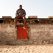Tekpe Hongah, a resident of Totope, a fishing village nearAda, Ghana, is pictured atop his home that is rapidly disappearing beneath the sand as the sea encroaches on the village. He has been forced to evacuate the house and move in with relatives. 7 March 2010