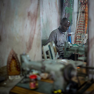 A tailor is seen in a mirror in  Lydie Malingumu's atelier, where all her dresser are tailored. CAPTA/FEDERICO SCOPPA
