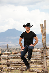 hot cowboy sitting on a ranch fence overlooking a mountain range