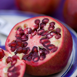 Pomegranate cut open on a blue plate