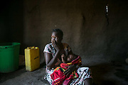 """Nyamai Billiew, 35, holds a baby called """"Sorry,"""" who was born from the rape, inside a hut in Bidibidi refugee settlement in Uganda.  She was raped by six Dinka soldiers in July 2016 when the fighting had erupted in Juba. When she was running towards the UN compound with her then three-year-old son, those soldiers stopped seven women including her and raped them. She hasn't heard about her husband or parents since then. The baby was born in Bidibidi camp."""