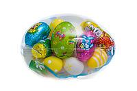 Gjennomsiktig påske-egg fylt med godteri. Helhvit bakgrunn.