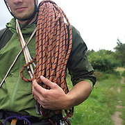 A man holds a rope used for climbing over his shoulder, Sutton Bank, North York Moors, North Yorkshire, UK